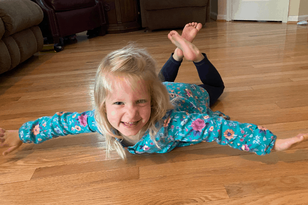 Girl laying on the floor in the superman position with her upper chest and arms, and legs off the ground demonstrating a core strengthening 5 minute activity for preschoolers.