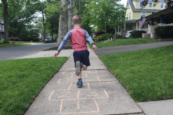 Boy demonstrating a 5 minute preschool gross motor activity for preschoolers doing a hopscotch board drawn so that he has to hop on one foot and then two feet repeatedly until the end.