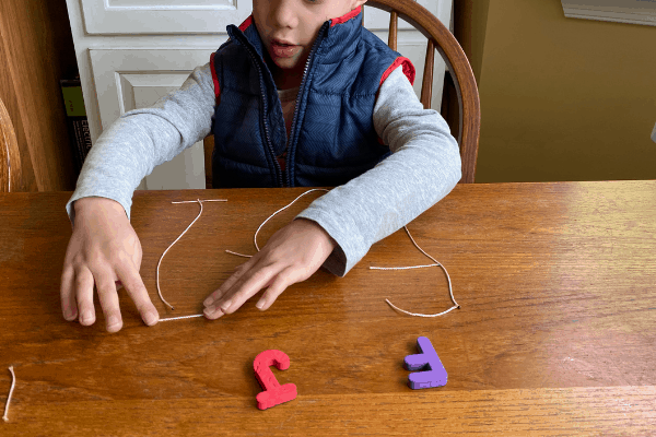Boy making letters out of string demonstrating a 5 minute preschool activity