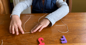 Child making letters out of string showing an example of a 5 Minute Preschool fine motor activity