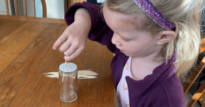 Child putting toothpicks through a hole of an empty spice container