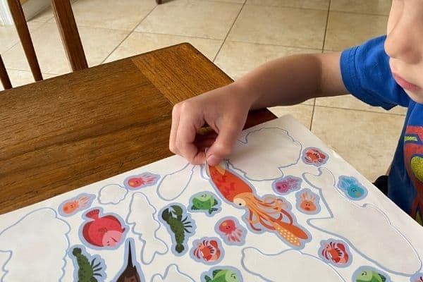 Boy peeling a reuseable sticker using a pincer grasp