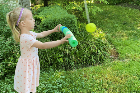Girl holding a pool noodle with different pieces of colored tape on hit, hitting a ball hanging from a tree with a specific color.