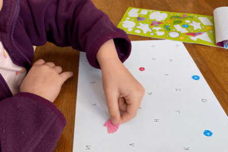 Child placing a sticker over a letter written on a piece of paper demonstrating an eye hand coordination game.