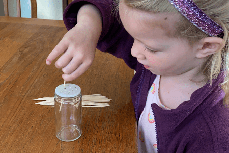 Preschooler putting a toothpick into a small hole of an empty spice jar container.